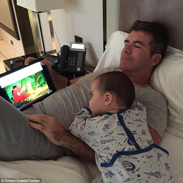 Cuddles: Simon Cowell shared a shot of himself watching The Lion King with his baby son, Eric, on Monday
