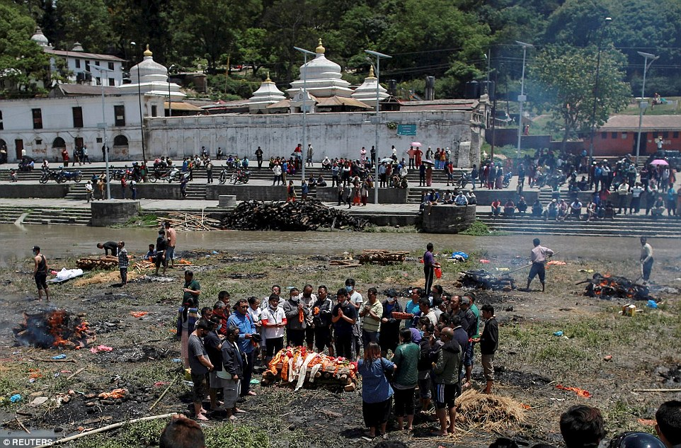 People pray before cremating the body of a victim of Saturday's earthquake, along a river in Kathmandu