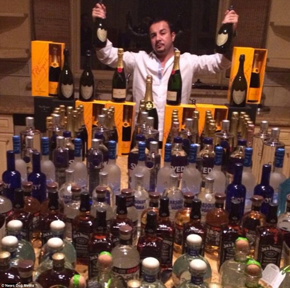 Bottoms up: Toutouni poses in front of dozens of bottles of spirit and champagne in this photo uploaded to his account