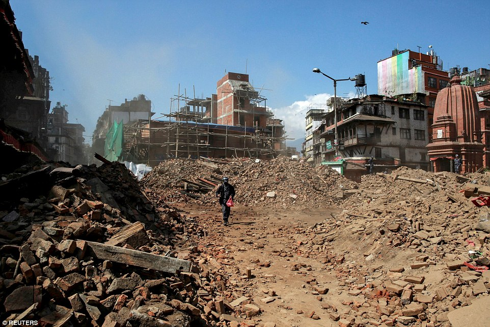A Nepalese police officer walks among the rubble of collapsed buildings after the earthquake in Kathmandu