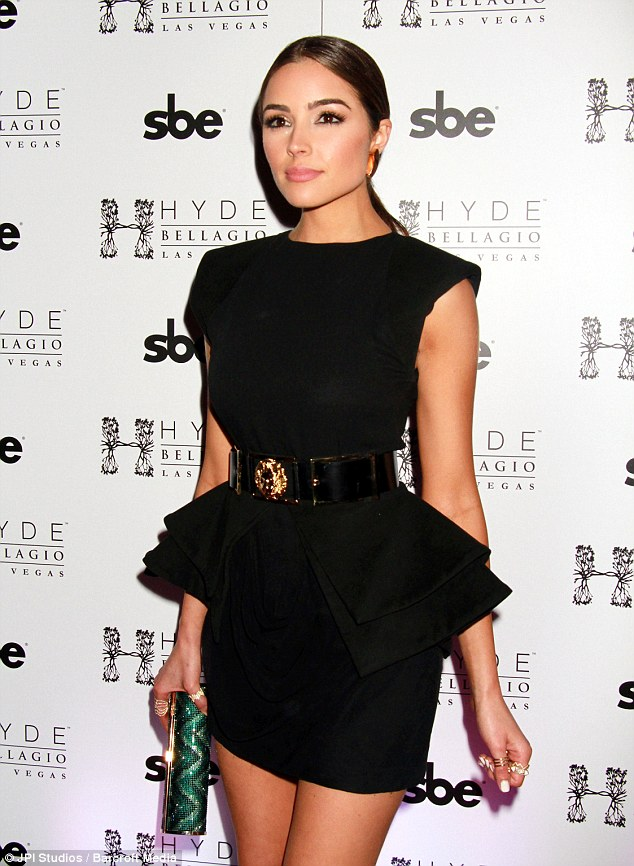 Bold: Olivia, also 22, oozed heaps of glamour in a striking black peplum dress, which boasted a short hemline and a large statement belt that clinched her waist