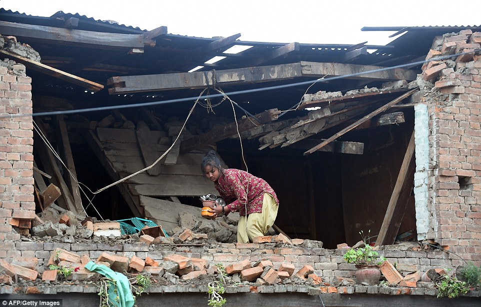 Taking stock: A Nepalese girl takes out belongings from her damaged house in Bhaktapur on the outskirts of Kathmandu