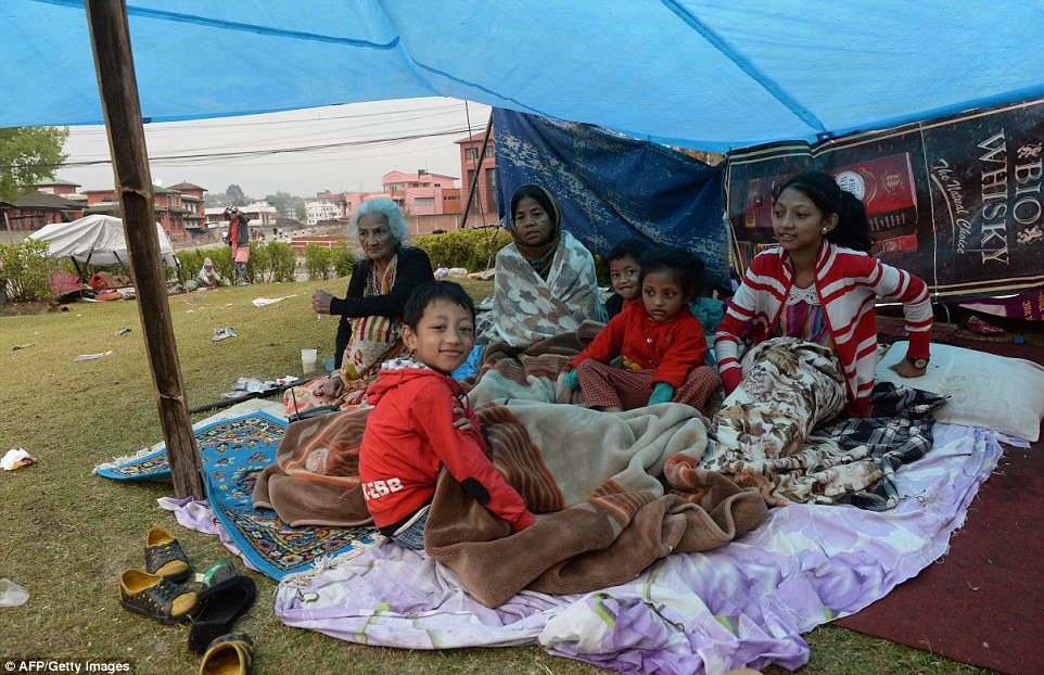 A Nepalese family rest in their makeshift shelter next to a road in Kathmandu two days after the quake
