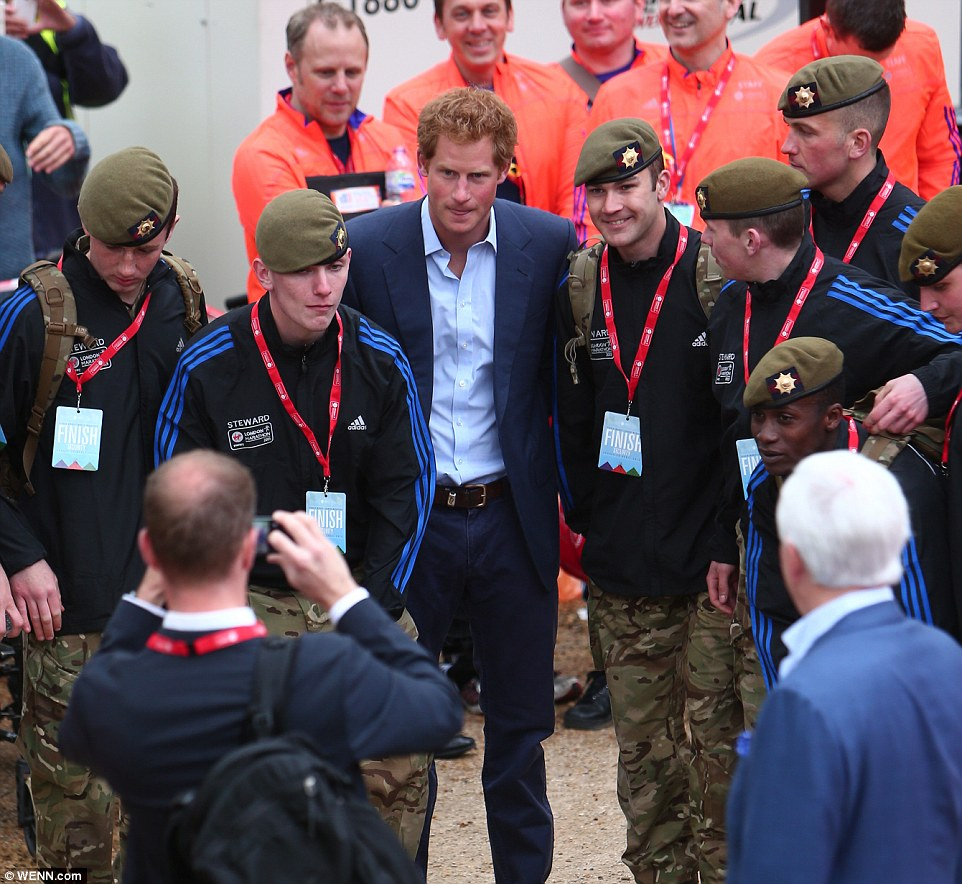 Prince Harry poses for a photo with members of the Armed Forces as he awaits to hand out medals to the winners of the elite races