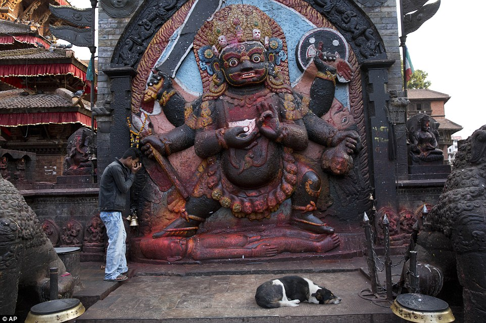 A man offers prayers to Hindu GodBhairav at Basantapur Durbar Square in Kathmandu as his loyal dog waits nearby. Many of the ancient city's temples were destroyed in the earthquake