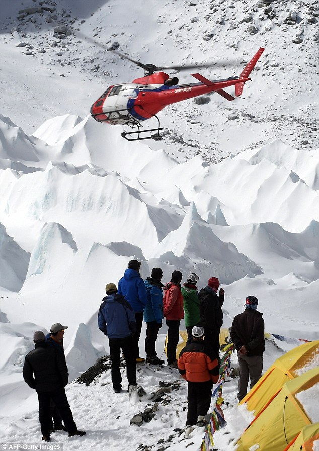 Nepali sherpas and members of expeditons watch as a rescue helicopter takes off with the injured on Sunday