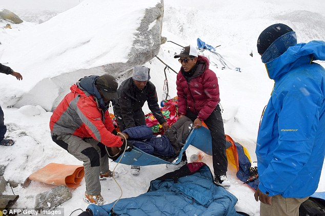 Rescuers help a porter onto a makeshift stretcher after he was injured when the wall of ice and snow hit