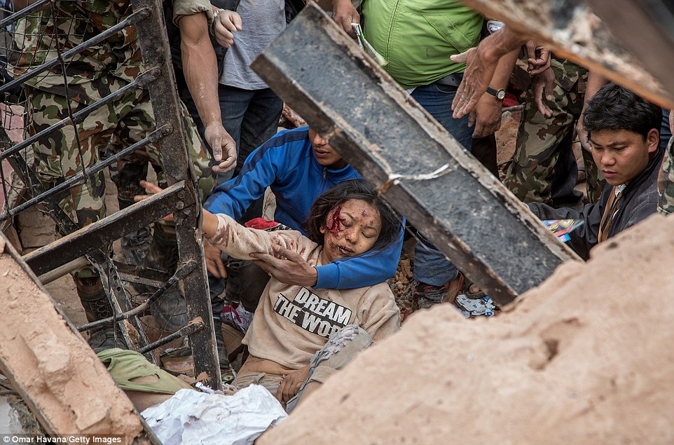 A survivor is pulled from the rubble of a collapsed building in Kathmandu yesterday shortly after the earthquake struck at around noon
