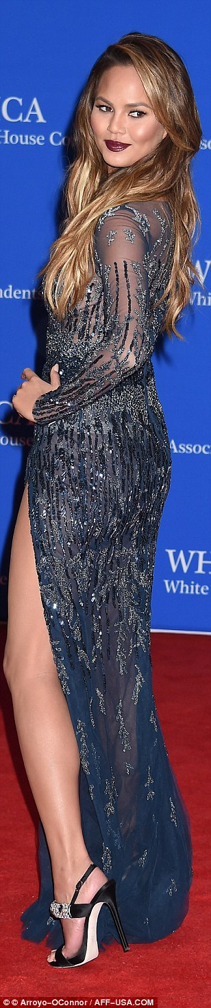 Stealing the show: Chrissy Teigem showed off some skin in a glamorous, glittering gown with a side-split