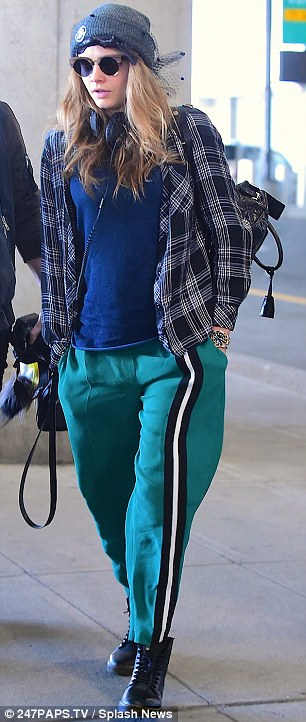 Casually cool: Cara was dressed casually for the trip, wearing a plaid shirt with green trousers and boots