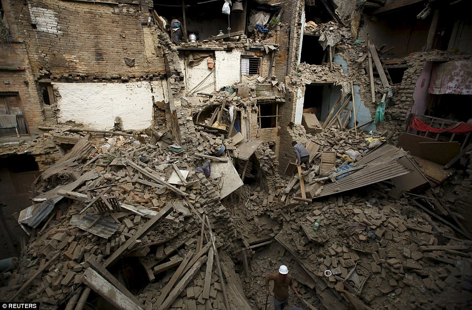 Men ease their way around the ruins of homes in Bhaktapur, scouring the site for any survivors. The death toll is expected to rise yet from 2,500