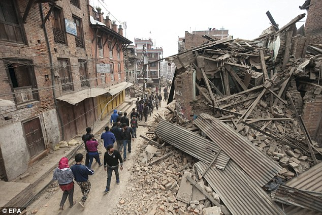 Residents are seen searching the remains of destroyed buildings as they deal with the aftermath