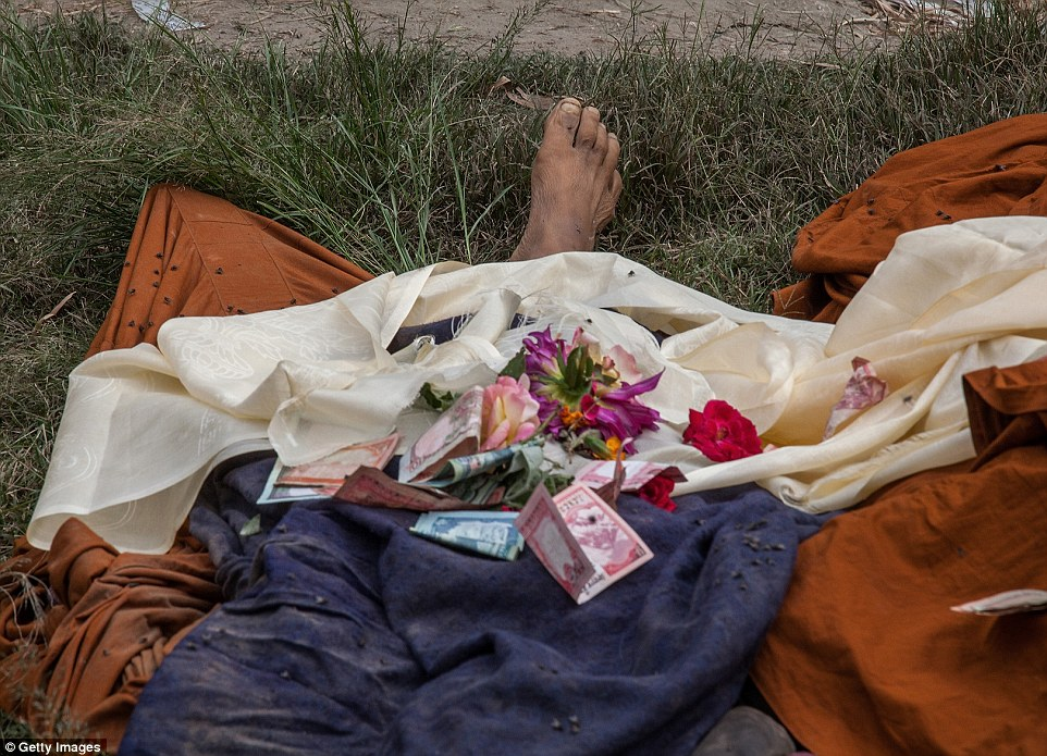 In Bhaktapur, flowers and money are left on the body of one of the earthquake's victims outside one of the city's overrun hospitals