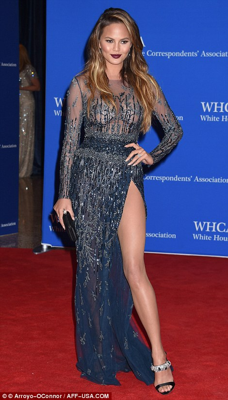 Model Chrissy Teigen shows off her slender leg in a sequined dress, which she teamed with a dark shade of red lipstick