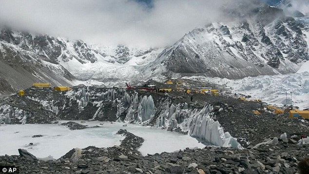 A helicopter attempts to land at Base Camp as it carries those injured and rescued from higher camps