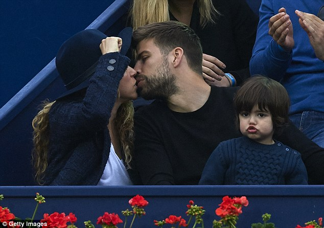 In love: Shakira and Gerard Pique enjoyed a loving embrace while attending the Barcelona Open with their first-born, Milan, at the weekend