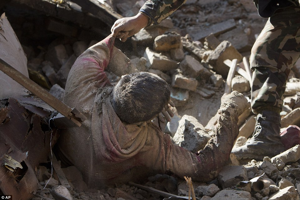 Members of the Nepalese army pull a dead body from the rubble of a collapsed building in Kathmandu