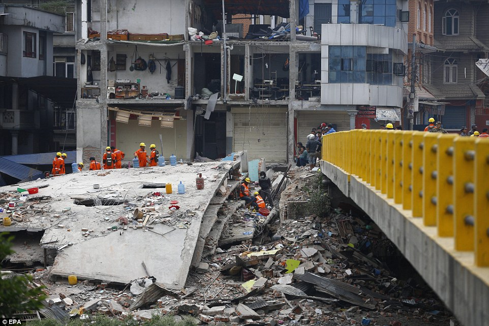 Rescue teams search through the ruins for survivors after one side of a building collapsed in central Kathmandu