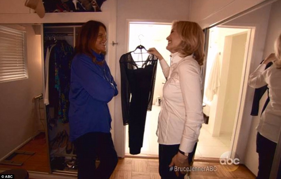 Glamorous dresser: Bruce is pictured showing Diane one of his dresses, a black number with see-through panels on its arms and neck