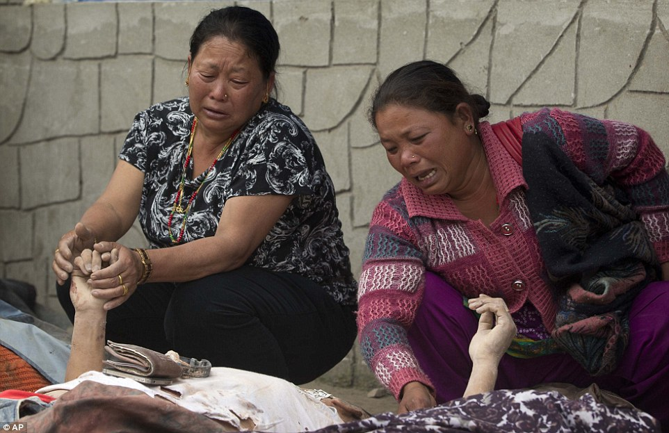 Grieving women hold the hands of relatives as they lie beneath a thin white sheet in the city of Kathmandu. Makeshift funeral pyres are being set up across the city