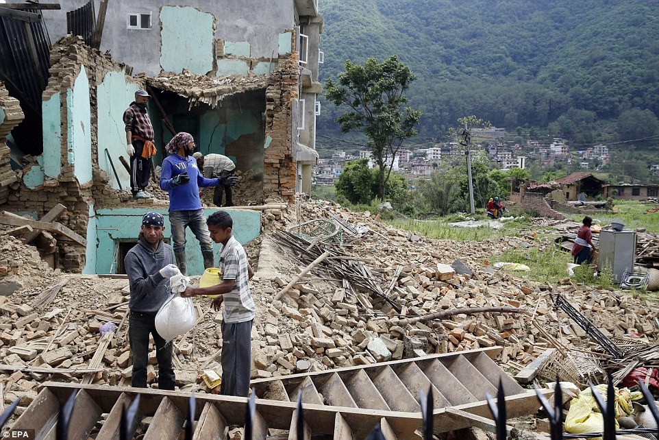Salvaging their life's possessions: People collect their remaining belongings and food from the rubble after the earthquake that destroyed homes in Kumalpur village, on the outskirts of capital Kathmandu