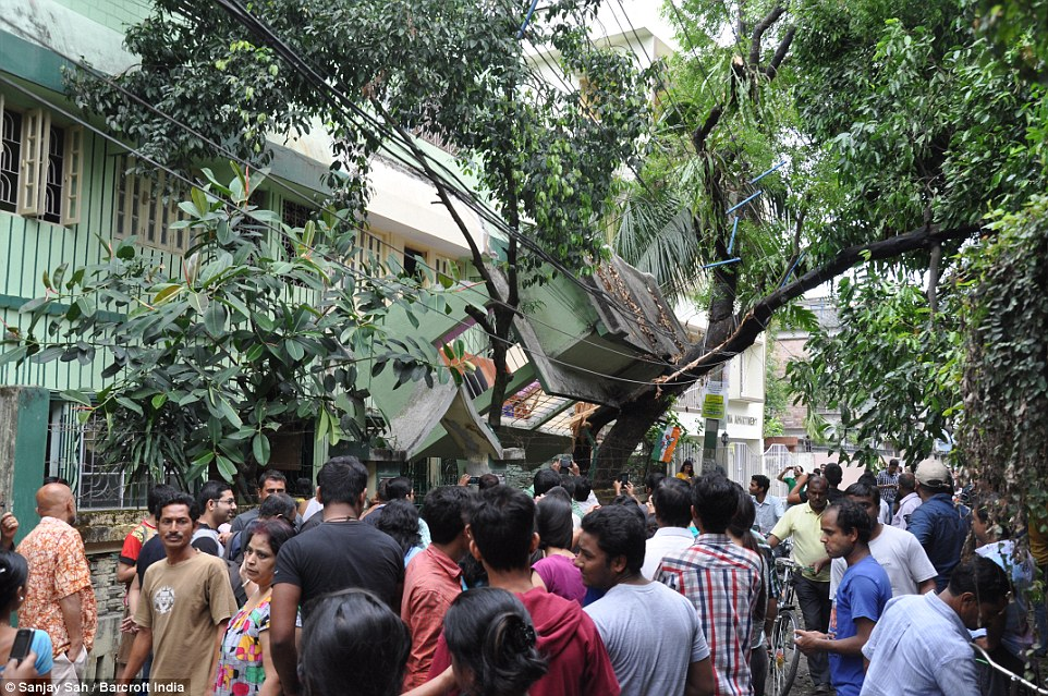 In Siliguri, India, where at least two people including a woman were killed, the front of an earthquake-damaged house has become trapped in wiring and the branches of a tree