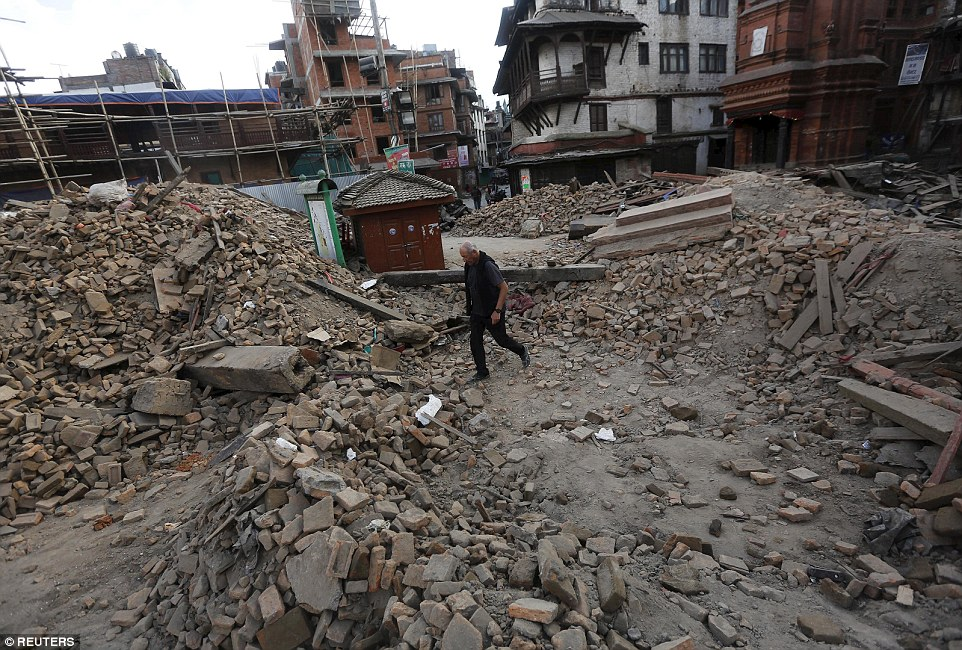 Debris: A tourist makes his way through the debris of a temple after an earthquake in Kathmandu