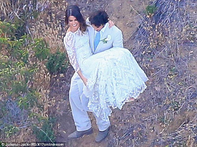 True gent: The handsome chap carried his bride down a muddy slope to ensure her dress didn't get dirty