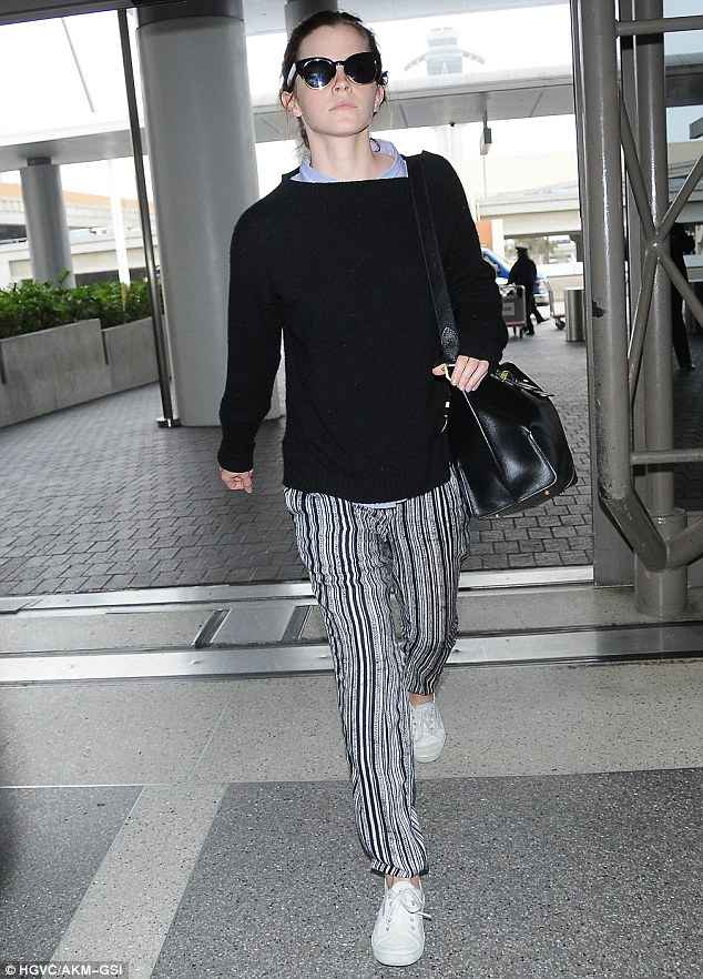 Monochrome look:Dressed down in a black sweater,dark sunglasses and stripy black and white trousers, she marched through the departures lounge to board the plane