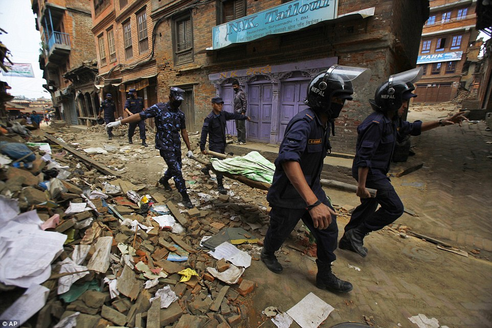 Police carry the body of another victim through the rubble-strewn streets of Bhaktapur. The earthquake is the worst disaster the country has seen for more than 80 years