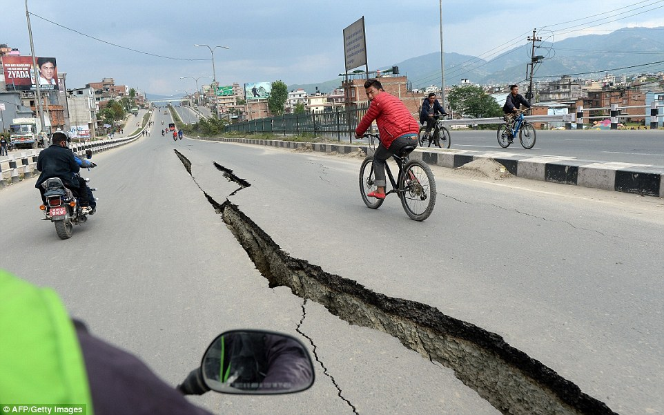 A near-empty road on the outskirts of Kathmandu is divided by a crack caused when the earthquake struck. Cyclists and motorists are the few to brave travelling on it the day after the disaster