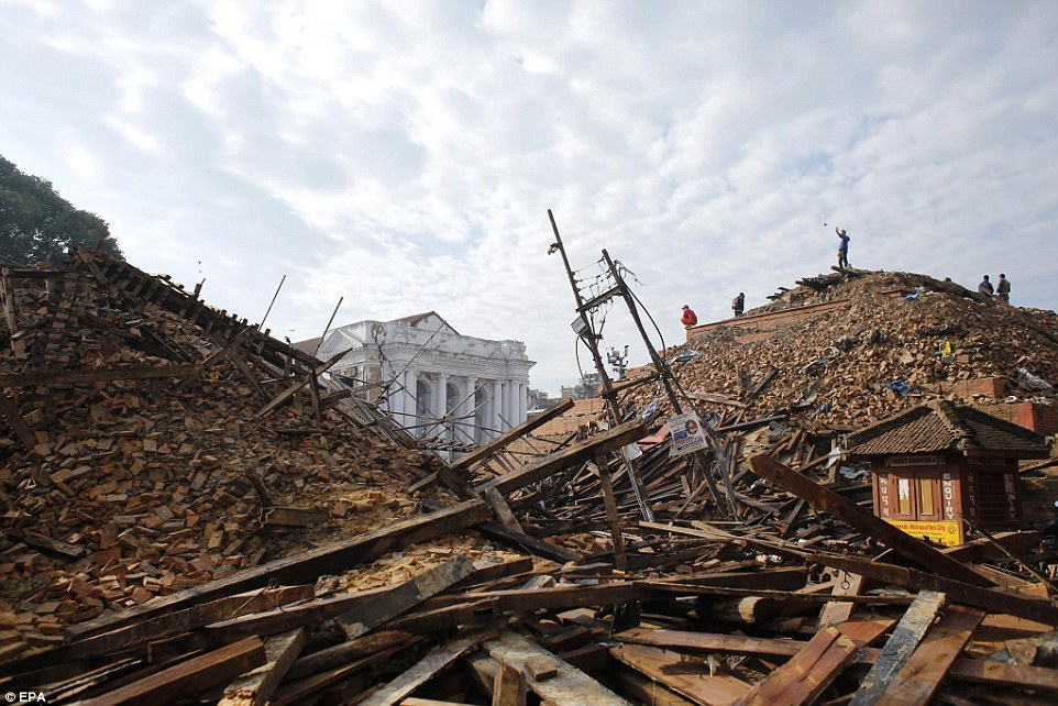 Reduced to rubble: Nepalis gather at the top of large mound where a temple once stood to view the scene of devastation in Kathmandu afterthe 7.9-magnitude quake hit the Nepalese capital
