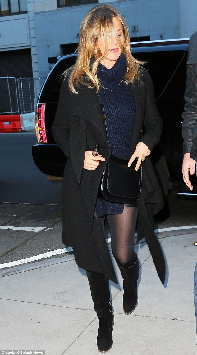 A black coat, knee-high black boots and a black leather cross-body bag completed the ensemble
