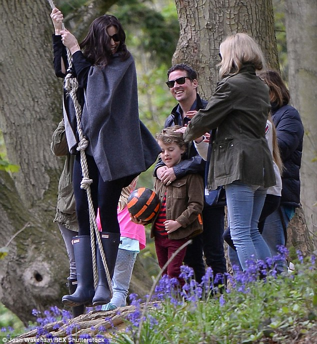 Having a giggle: Liv really let her hair down as she swung on a rope while the others looked on