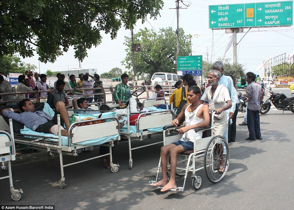 Precautions: Patients and their attendants are seen being treated outside hospital after an aftershock hit the area on Sunday