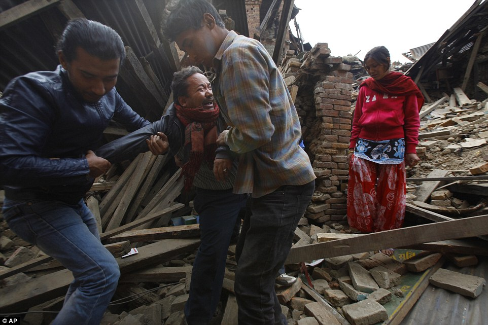 In Bhaktapur, a man weeps as he is pulled away from the site where his house once stood. The Kathmandu Valley is densely populated, with thousands living in close conditions