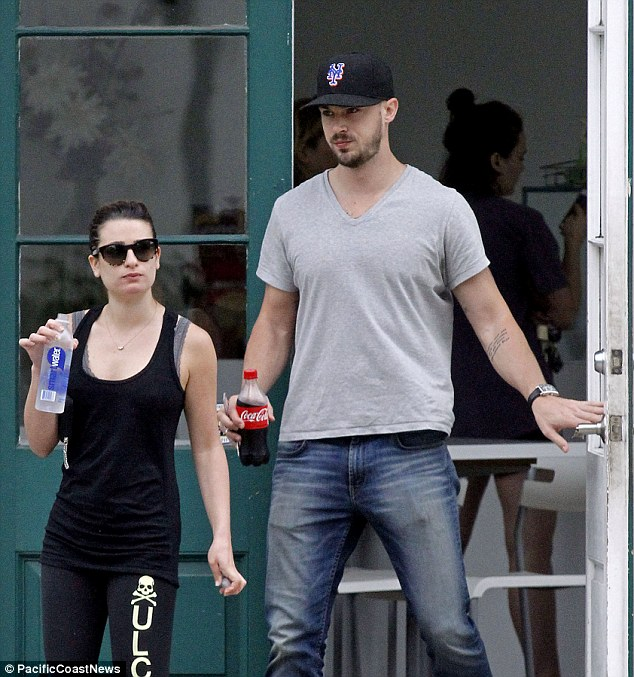 Casual: Her handsome beau, 29, kept things simple in a plain grey T-shirt and denim jeans, which he teamed with a dark baseball cap and white trainers