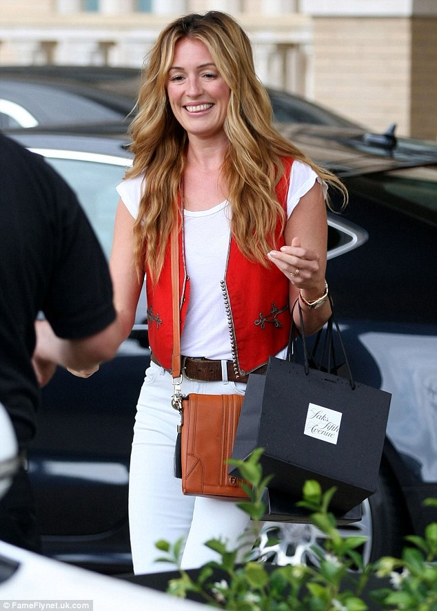 Wow thing: She brightened up an all-white ensemble with an orange waistcoat and a brown leather handbag