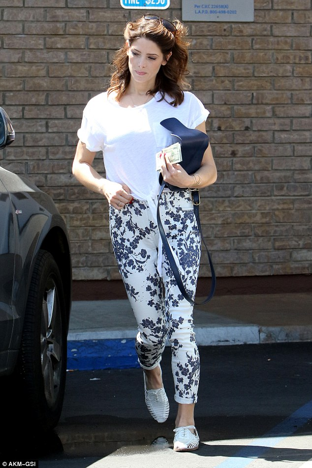 City chic: The 28-year-old actress confidently paraded her slender frame in tight floral trousers and a white tie-up pocket T-shirt