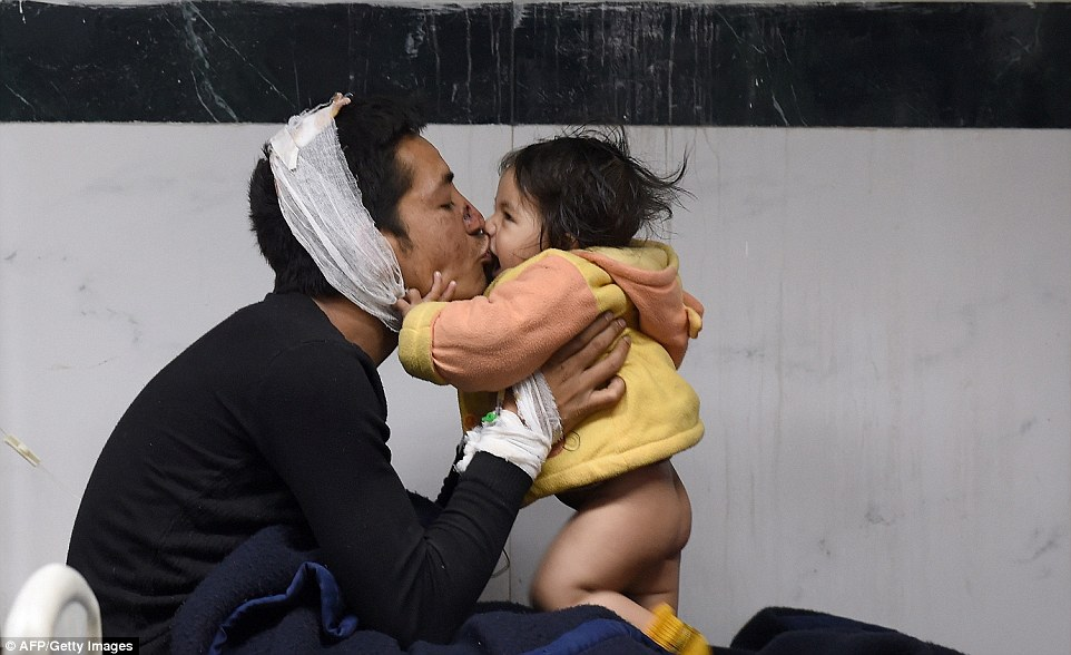 Suresh Parihar plays with his 8-month-old daughter Sandhaya as he is treated for injuries sustained in an earthquake at a city hospital in the city of Kathmandu