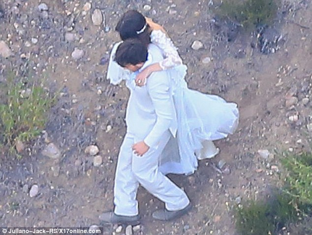 A little assistance: The 26-year-old held onto her man as she navigated her way down a gravelly slope