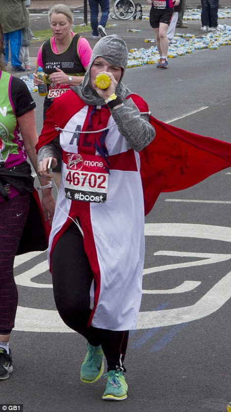 One runner takes a swig of juice at the 10-mile mark of the race