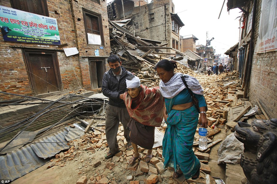 An elderly woman is accompanied through the street in the Bhaktapur after undergoing treatment for a head injury at one of its remaining hospitals