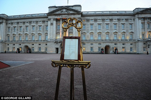 ...before being displayed on the traditional easel inside the gates of Buckingham Palace