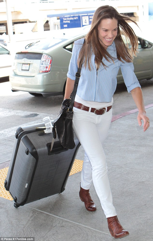 Ready to fly: Hilary Swank pulled a large suitcase behind her as she headed to a plane at the Los Angeles International Airport on Sunday