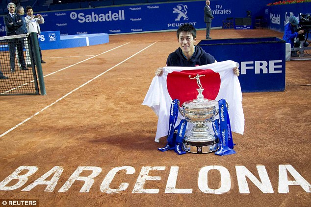 Nishikori holds up the Japanese flag with the trophy after his second straight Barcelona Open title success