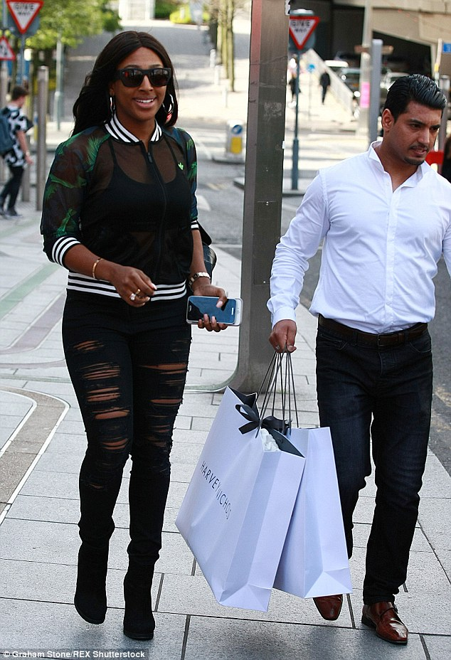 Helping hand: An assistant carried the singer's purchases to her car after her shopping spree