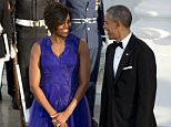 President Barack Obama and first lady Michelle Obama smile at each other as they wait to greet Japanese Prime Minister Shinzo Abe and his wife Akie Abe at the North Portico of the White House as they arrive for a state dinner, Tuesday, April 28, 2015, in Washington. (AP Photo/Jacquelyn Martin)