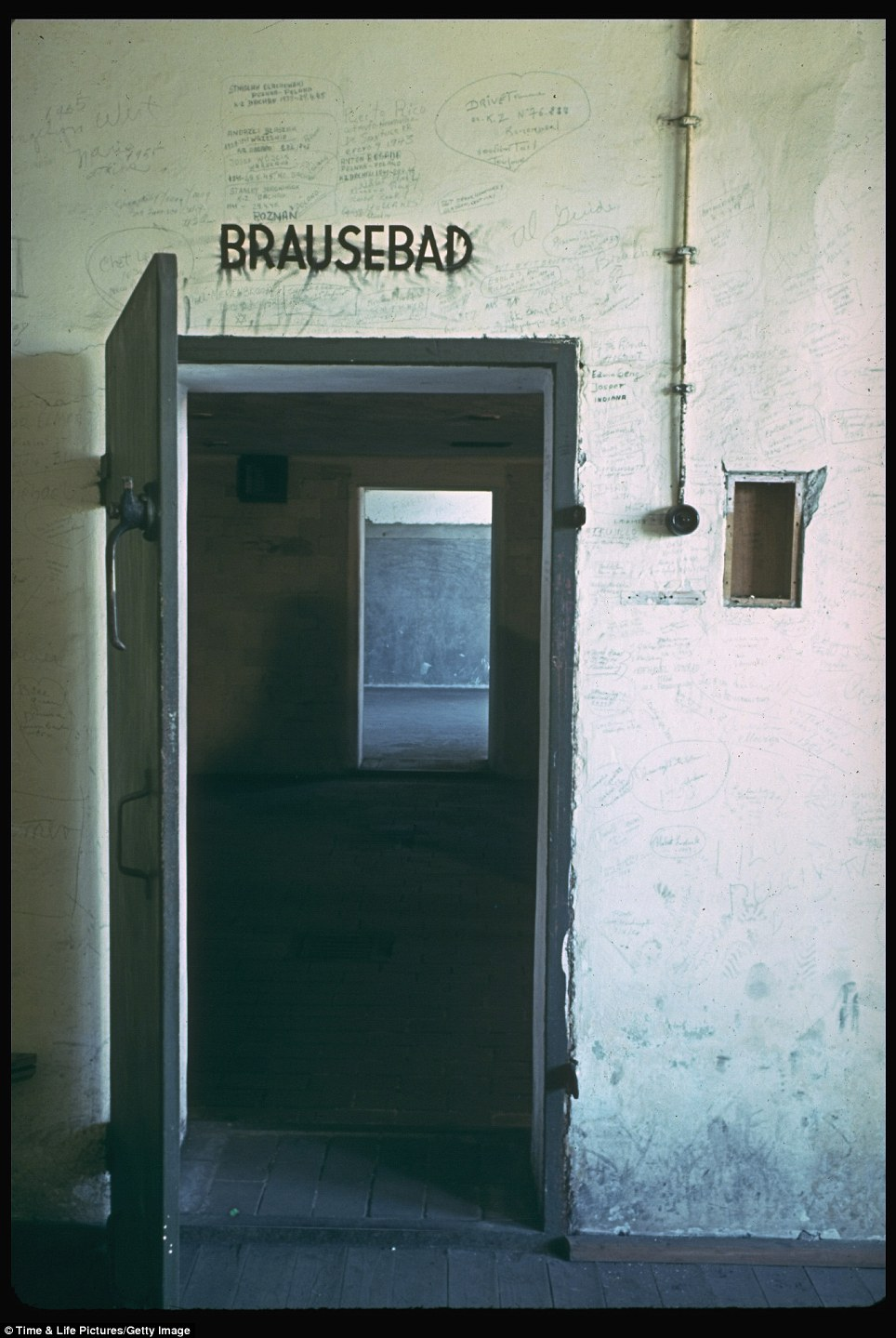 The Brausebad - shower - sign hangs over a door surrounded by graffiti. The doorway led to the gas chamber
