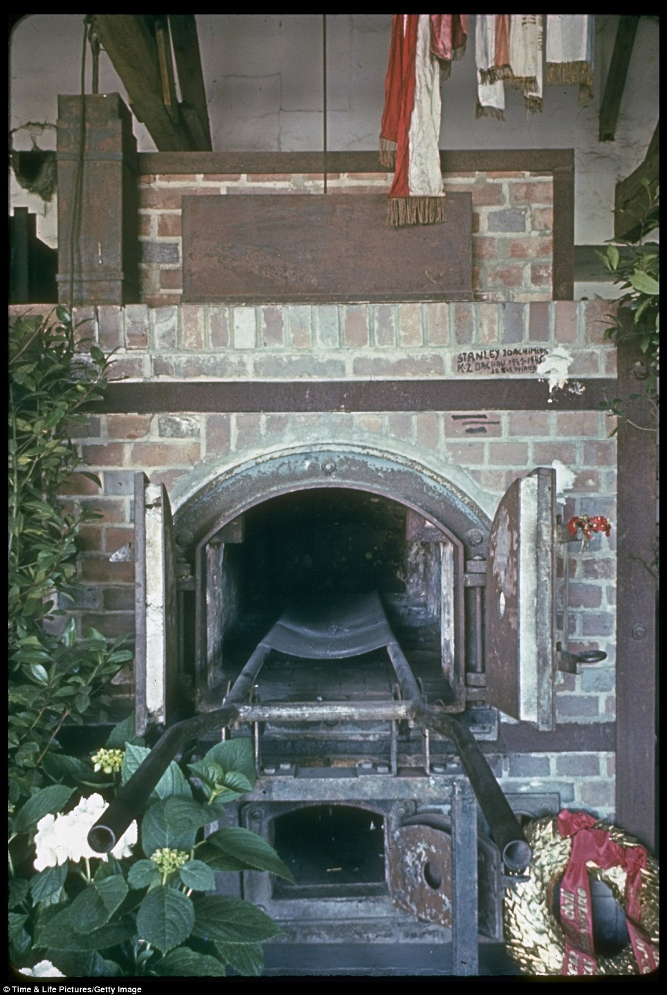 Prayer scarves and wreathes surround one of the crematoriums in Dachau